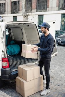 Entregador feliz segurando a caixa de papelão perto de veículo