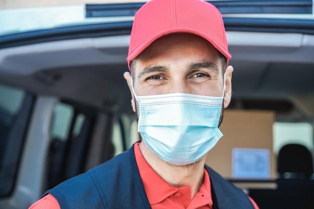 Entregador hispânico sorrindo para a câmera enquanto usa máscara de segurança - foco no rosto