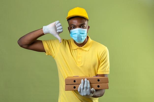 Entregador homem afro-americano com camisa pólo amarela e boné, máscara protetora médica, segurando caixas de pizza com um sorriso no rosto mostrando o polegar para baixo em pé no verde