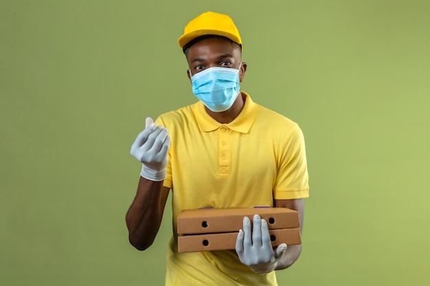 Entregador homem afro-americano com camisa pólo amarela e boné, máscara protetora médica, segurando caixas de pizza, fazendo gesto de dinheiro com a mão esperando o pagamento em pé no verde