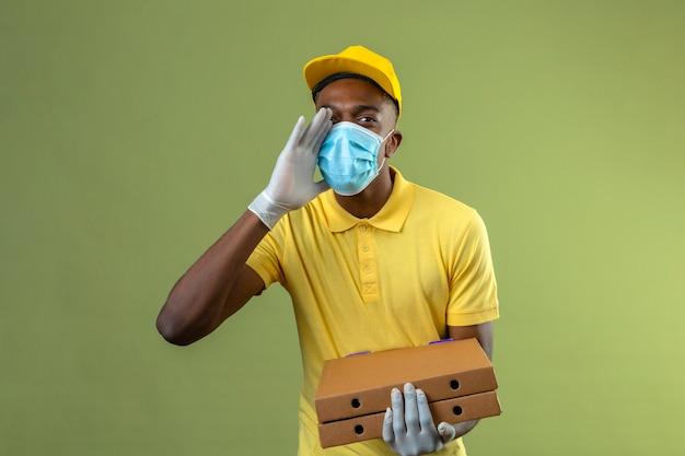 Entregador homem afro-americano com camisa pólo amarela e boné, usando máscara protetora médica, segurando caixas de pizza gritando ou chamando alguém com a mão perto da boca em pé no verde