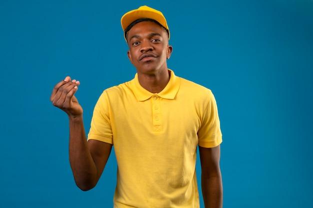Entregador homem afro-americano de camisa pólo amarela e boné fazendo gesto de dinheiro com a mão sorrindo no azul isolado