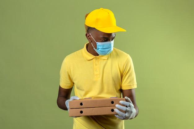 Entregador homem afro-americano de camisa pólo amarela e boné, máscara protetora médica, segurando caixas de pizza, olhando para o lado com cara séria de pé no verde