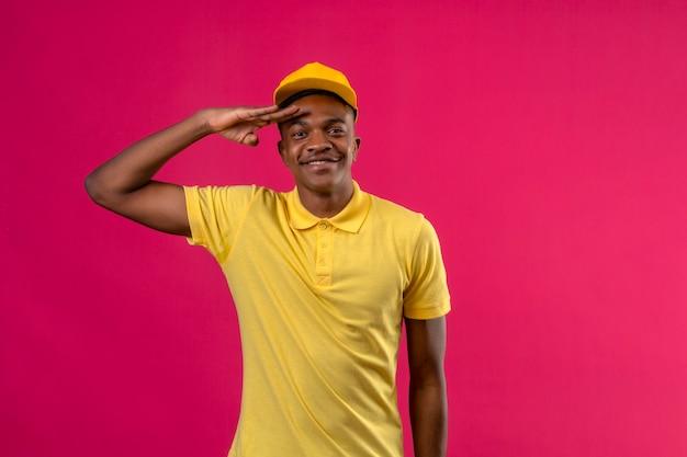 Entregador homem afro-americano de camisa pólo amarela e boné saudando, parecendo confiante, sorrindo em pé na rosa isolada