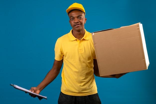 Entregador homem afro-americano de camisa pólo amarela e boné segurando a prancheta e uma caixa de papelão, sorrindo amigável em pé na laranja isolada