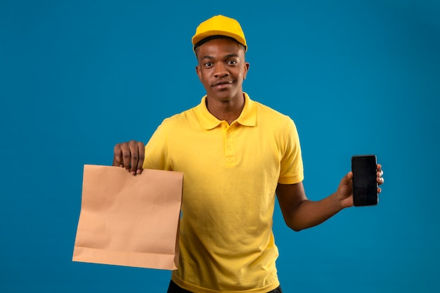 Entregador homem afro-americano de camisa pólo amarela e boné segurando um pacote de papel mostrando o celular com um sorriso no rosto parado no azul