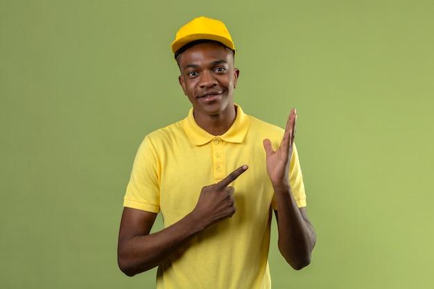 Entregador homem afro-americano de camisa pólo amarela e boné sorrindo enquanto se apresenta com a mão e aponta com o dedo em pé no verde