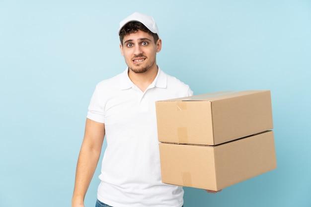 Entregador homem caucasiano isolado em azul tendo dúvidas e com expressão facial confusa