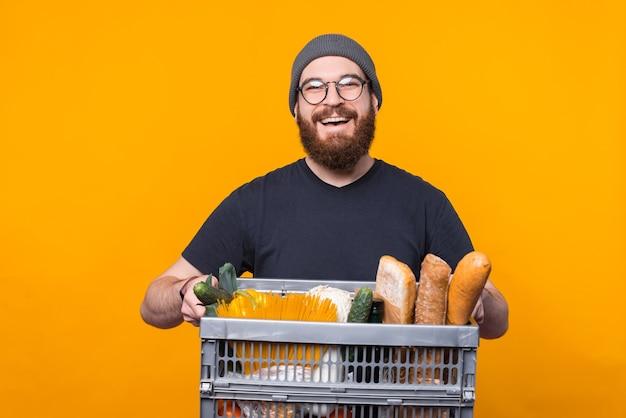 Entregador jovem alegre está segurando uma cesta cheia de comida e mercearia.