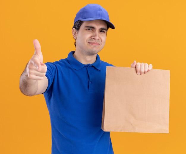 Entregador jovem confiante de uniforme azul e boné segurando um pacote de papel, olhando e apontando para frente, isolado na parede laranja