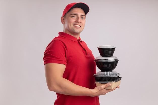 Entregador jovem confiante vestindo uniforme com tampa segurando recipientes de comida isolados na parede branca