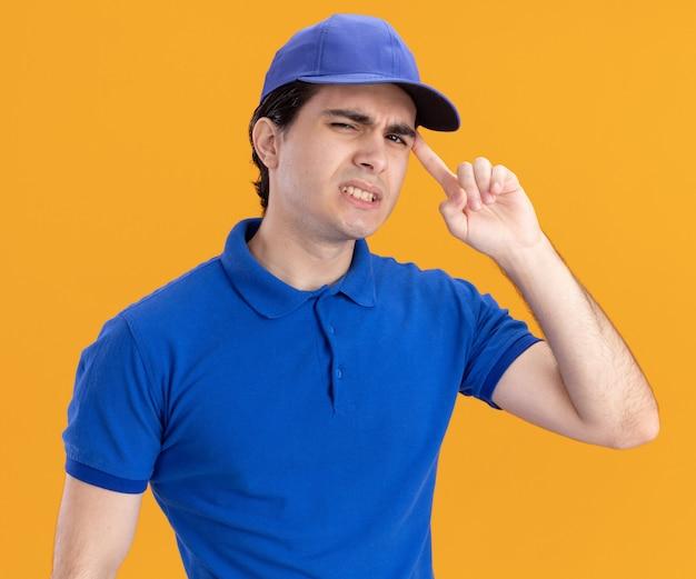 Entregador jovem confuso de uniforme azul e boné olhando para frente fazendo gesto de pensar isolado na parede laranja
