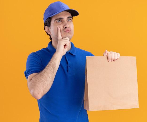 Entregador jovem confuso de uniforme azul e boné segurando um pacote de papel olhando para o lado, colocando a mão no queixo franzindo os lábios isolados na parede laranja