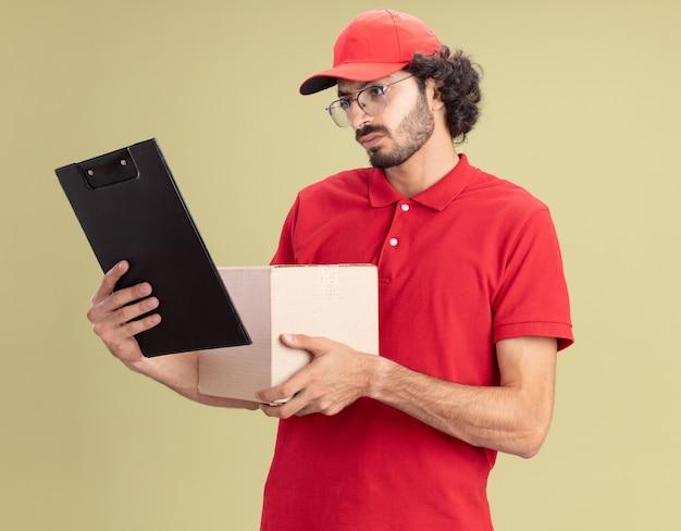 Entregador jovem confuso de uniforme vermelho e boné de óculos segurando uma caixa de papelão e uma prancheta, olhando para a prancheta isolada na parede verde oliva
