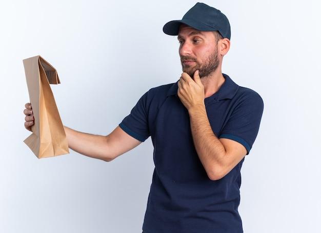 Entregador, jovem, duvidoso, caucasiano, de uniforme azul e boné, segurando a mão no queixo, esticando-se e olhando para um pacote de papel isolado na parede branca