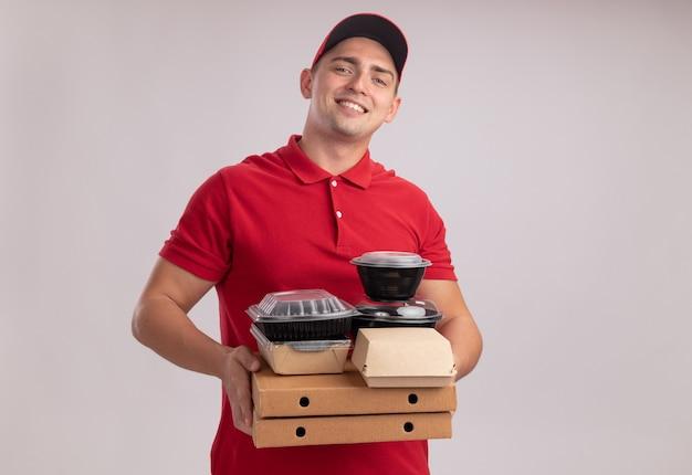 Entregador jovem sorridente, vestindo uniforme com tampa, segurando recipientes de comida em caixas de pizza isoladas na parede branca