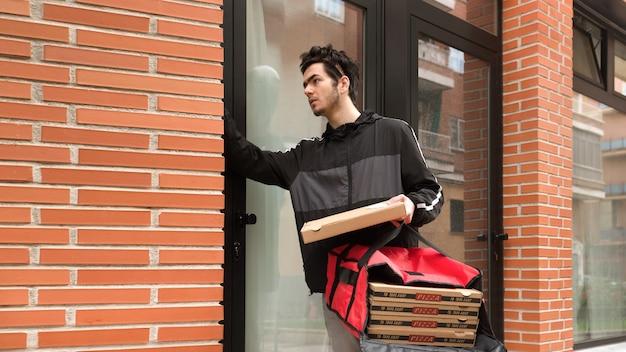 Entregador ligando para o porteiro, segurando uma sacola vermelha para entrega em domicílio