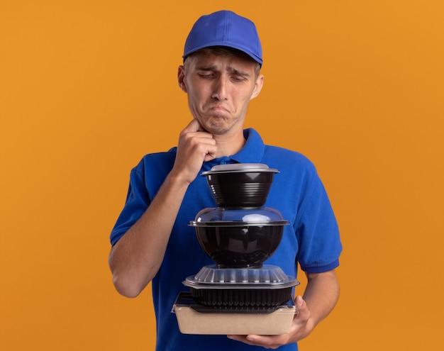 Entregador loira jovem e triste segurando e olhando para recipientes de comida em laranja