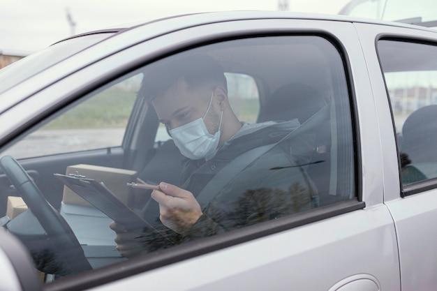 Entregador masculino com máscara e pacotes
