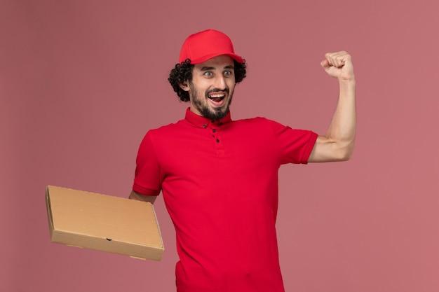 Entregador masculino de camisa vermelha e capa, vista frontal, segurando a caixa de entrega de comida e regozijando-se com o funcionário da empresa de entrega de serviço de parede rosa
