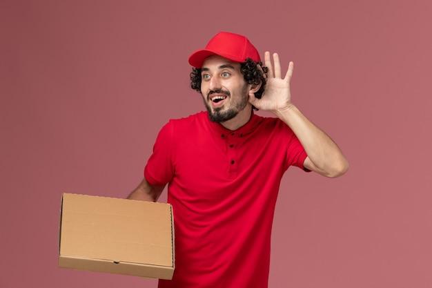 Entregador masculino de camisa vermelha e capa, vista frontal, segurando a caixa de entrega de comida na parede rosa, funcionário da empresa de serviço de entrega