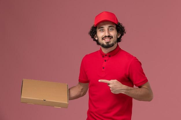 Entregador masculino de camisa vermelha e capa, vista frontal, segurando a caixa de entrega de comida na parede rosa trabalho de funcionário da empresa de entrega de serviço