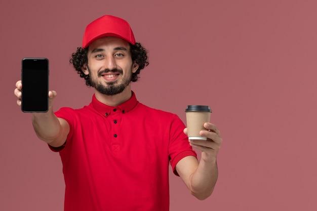 Entregador masculino de camisa vermelha e capa, vista frontal, segurando a xícara de café marrom e o telefone na parede rosa claro.