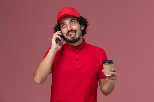 Entregador masculino de camisa vermelha e capa, vista frontal, segurando a xícara de café marrom, falando ao telefone na parede rosa.
