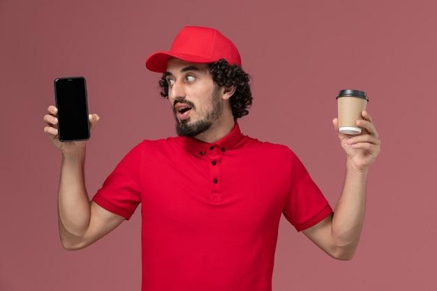 Entregador masculino de camisa vermelha e capa, vista frontal, segurando uma xícara de café marrom e telefone na parede rosa claro, trabalho de funcionário de entrega de serviço