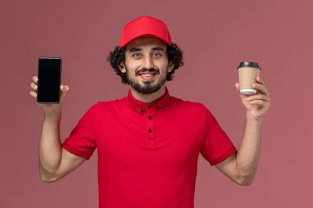 Entregador masculino de camisa vermelha e capa, vista frontal, segurando uma xícara de café marrom e telefone na parede rosa claro.