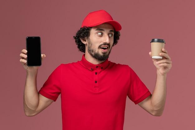 Entregador masculino de camisa vermelha e capa, vista frontal, segurando uma xícara de café marrom e um telefone na parede rosa claro.