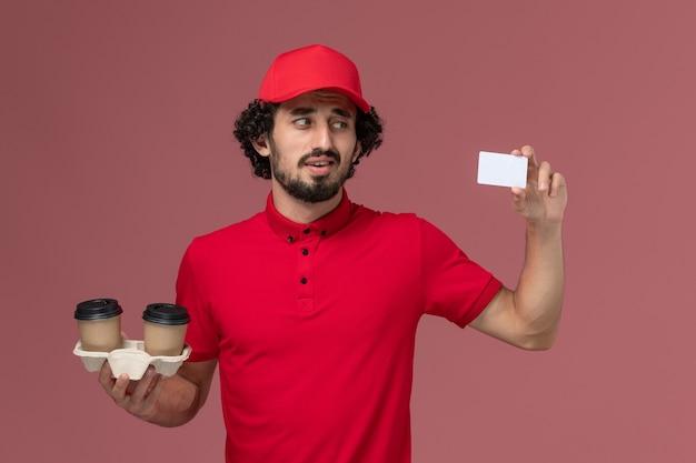 Entregador masculino de camisa vermelha e capa, vista frontal, segurando xícaras de café marrom e cartão na parede rosa claro, trabalho de funcionário de entrega de serviço