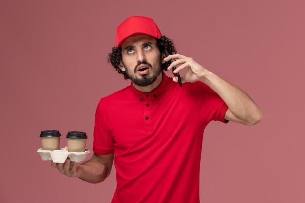 Entregador masculino de camisa vermelha e capa, vista frontal, segurando xícaras de café marrom e falando ao telefone na parede rosa claro.