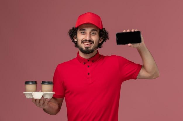Entregador masculino de camisa vermelha e capa, vista frontal, segurando xícaras de café marrom e telefone na parede rosa claro, trabalho de funcionário de entrega de serviço