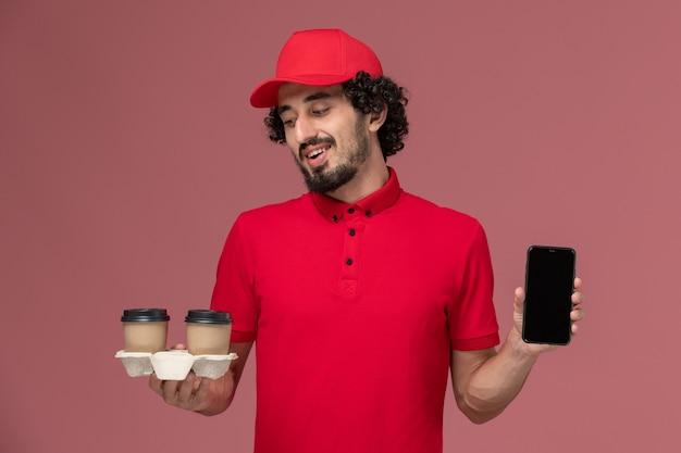 Entregador masculino de camisa vermelha e capa, vista frontal, segurando xícaras de café marrom e telefone na parede rosa claro.