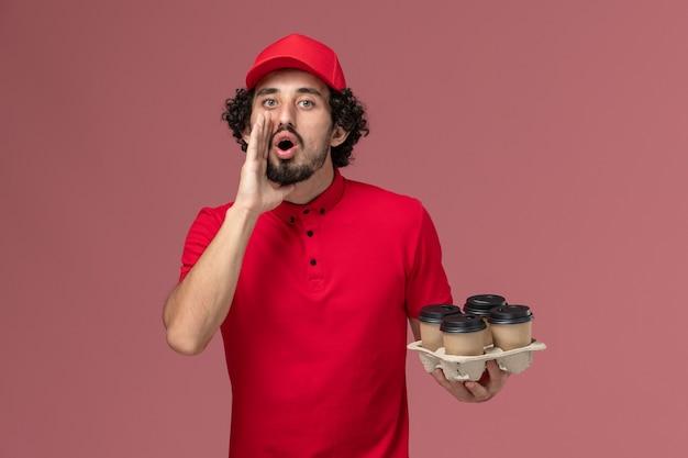 Entregador masculino de camisa vermelha e capa, vista frontal, segurando xícaras de café marrons e chamando funcionário de entrega de serviço de parede rosa claro