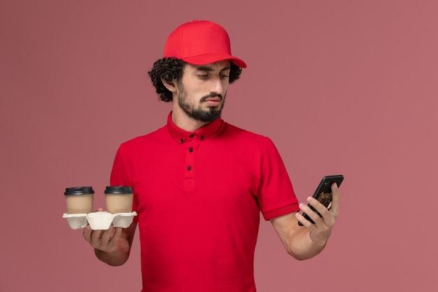 Entregador masculino de camisa vermelha e capa, vista frontal, segurando xícaras de café marrons e telefone na parede rosa claro funcionário de entrega de serviço masculino