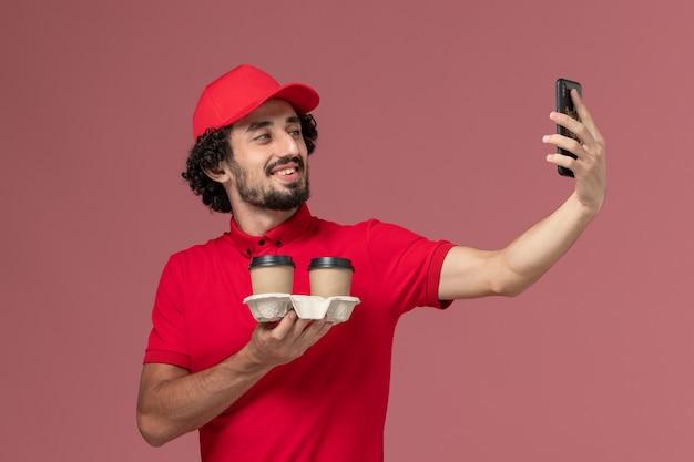 Entregador masculino de camisa vermelha e capa, vista frontal, segurando xícaras de café marrons e tirando uma selfie na parede rosa claro.