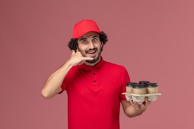 Entregador masculino de camisa vermelha e capa, vista frontal, segurando xícaras de café marrons na parede rosa claro empresa de funcionário de entrega de serviço masculino