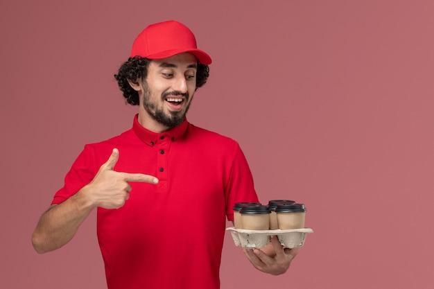 Entregador masculino de camisa vermelha e capa, vista frontal, segurando xícaras de café marrons na parede rosa claro funcionário de entrega de serviço