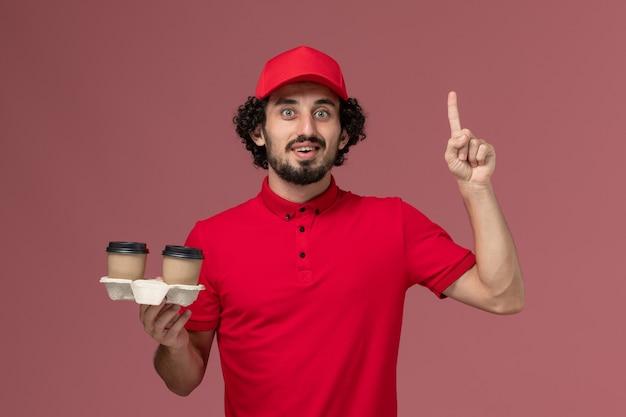 Entregador masculino de camisa vermelha e capa, vista frontal, segurando xícaras de café marrons na parede rosa trabalhador de entrega de serviço