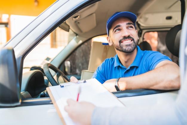 Entregador na van, enquanto o cliente assina a área de transferência.
