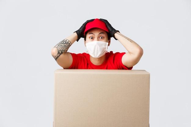 Entregador nervoso com máscara médica e luvas de proteção trabalha muito durante a pandemia, enquanto os clientes fazem pedidos em lojas online, apoiam-se em uma caixa de papelão e olham ansiosamente para a câmera