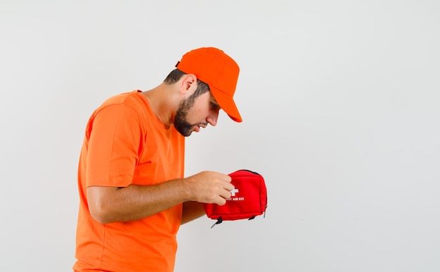 Entregador olhando atentamente para o kit de primeiros socorros em camiseta laranja, boné.