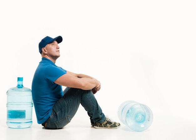 Entregador posando com garrafas de água e copie o espaço