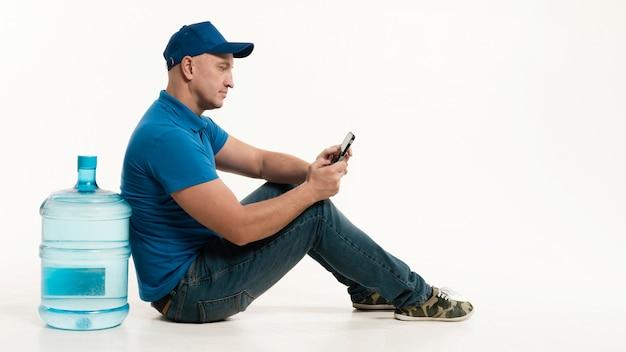 Entregador, posando para o lado, mantendo o smartphone