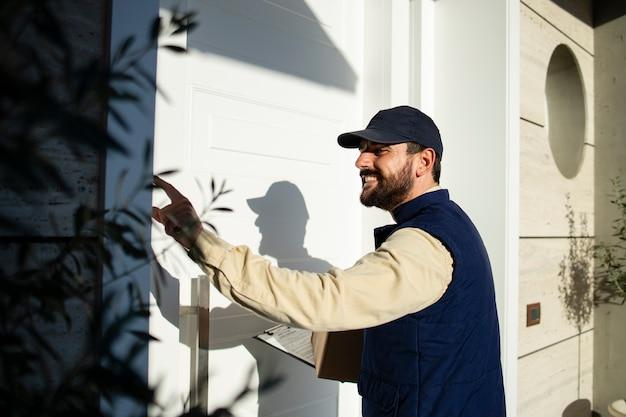 Entregador profissional tocando campainha e entregando pacotes rapidamente no endereço correto.