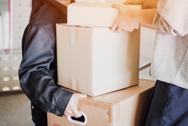 Entregador recebe o pacote da caixa do pacote para o cliente