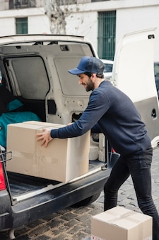 Entregador, removendo o pacote do veículo