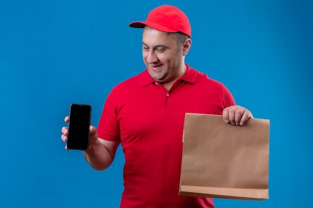 Entregador satisfeito vestindo uniforme vermelho e boné segurando um pacote de papel mostrando um celular sorrindo com uma cara feliz em pé sobre um fundo azul